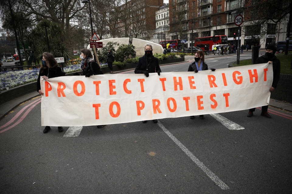 Demonstrators holding a banner block traffic during a 'Kill the Bill' protest in London, Saturday, April 3, 2021. The demonstration is against the contentious Police, Crime, Sentencing and Courts Bill, which is currently going through Parliament and would give police stronger powers to restrict protests. (AP Photo/Matt Dunham)