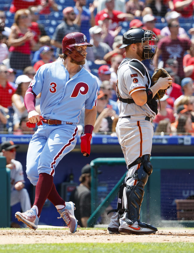 Philadelphia Phillies' Bryce Harper, left, comes in to score on the hit by Scott Kingery as San Francisco Giants catcher Stephen Vogt, right, looks on during the third inning of a baseball game, Thursday, Aug. 1, 2019, in Philadelphia. (AP Photo/Chris Szagola)
