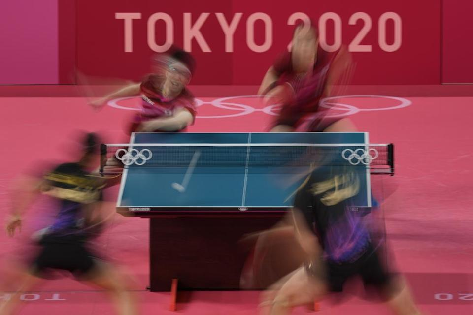 Japan's Mima Ito, left, and Jun Mizutani compete during the table tennis mixed doubles gold medal match against China's Xu Xin and Liu Shiwen.