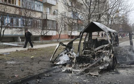 A man walks past a burnt-out vehicle after a shelling by pro-Russian rebels of a residential sector in Mariupol