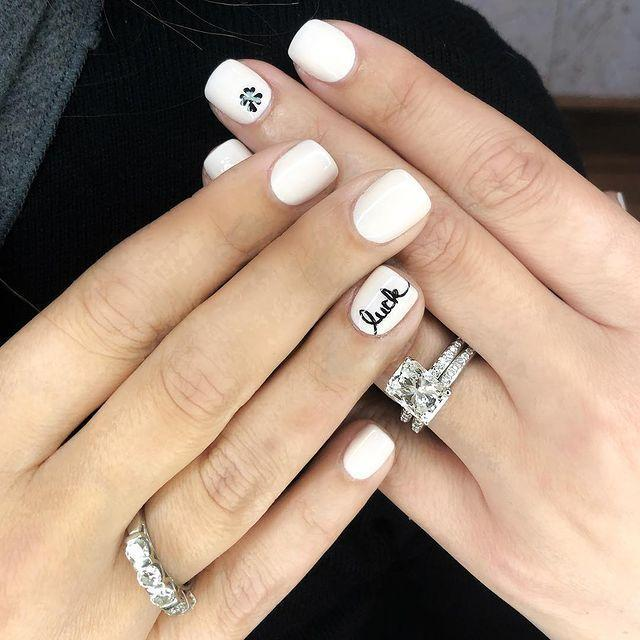 """<p>With a clean, white base and small, black accents, this is the most minimalist mani on our list — if that's your thing. A nail pen will give you the precision to recreate that tiny text.</p><p><a class=""""link rapid-noclick-resp"""" href=""""https://www.amazon.com/Sally-Hansen-Creating-Radiant-without/dp/B00HJIXAS0/?tag=syn-yahoo-20&ascsubtag=%5Bartid%7C10055.g.26310821%5Bsrc%7Cyahoo-us"""" rel=""""nofollow noopener"""" target=""""_blank"""" data-ylk=""""slk:SHOP NAIL PENS"""">SHOP NAIL PENS</a> </p><p><a href=""""https://www.instagram.com/p/BunAk7cHgKl/&hidecaption=true"""" rel=""""nofollow noopener"""" target=""""_blank"""" data-ylk=""""slk:See the original post on Instagram"""" class=""""link rapid-noclick-resp"""">See the original post on Instagram</a></p>"""