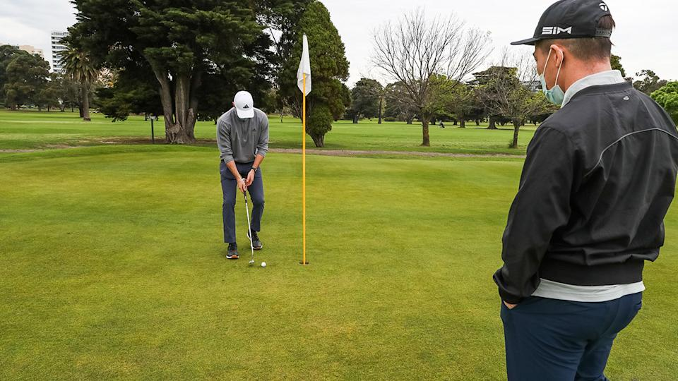 A golfer, pictured here putting at Albert Park Golf Course in Melbourne.