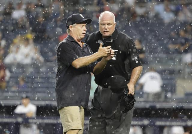 Home plate umpire Brian O'Nora, right, confers with New York Yankees Head Groundskeeper Danny Cunningham before calling a rain delay during the sixth inning of a baseball game between the New York Yankees and the Arizona Diamondbacks Wednesday, July 31, 2019, in New York. (AP Photo/Frank Franklin II)