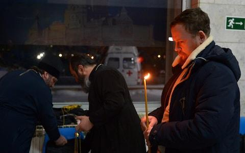 A man holds a candle at Orsk airport, the ill-fated plane's intended destination - Credit: TASS/Barcroft Images