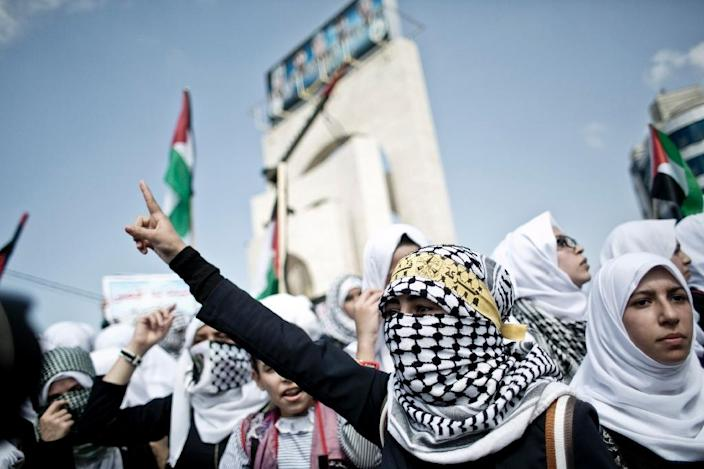Palestinian schoolgirls, some wearing the trademark black-and-white keffiyeh, shout slogans during an anti-Israel protest in the southern Gaza Strip town of Rafah on October 14, 2015 (AFP Photo/Said Khatib)