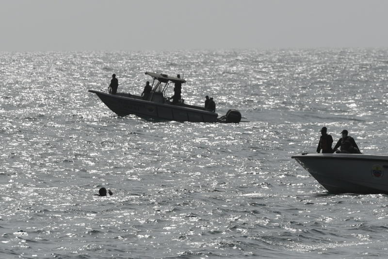 Security forces investigate near the shore in the port city of La Guaira, Venezuela, Sunday, May 3, 2020. Interior Minister Nestor Reverol said on state television that security forces overcame before dawn Sunday an armed maritime incursion with speedboats from neighboring Colombia in which several attackers were killed and others detained. (AP Photo/Matias Delacroix)