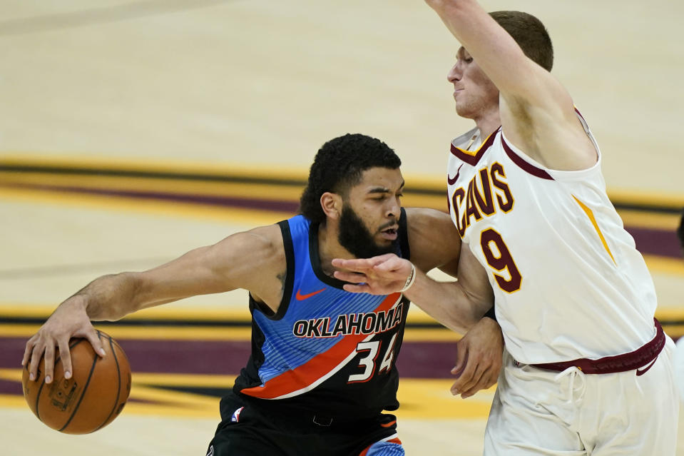 Oklahoma City Thunder's Kenrich Williams (34) drives against Cleveland Cavaliers' Dylan Windler (9) in the second half of an NBA basketball game, Sunday, Feb. 21, 2021, in Cleveland. Oklahoma won 117-101.(AP Photo/Tony Dejak)