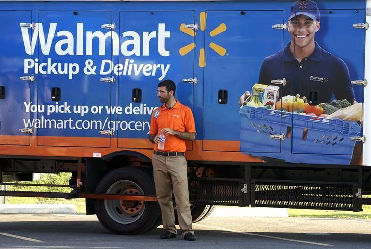 A Wal-Mart Pickup-Grocery employee waits next to a truck at a test store in Bentonville