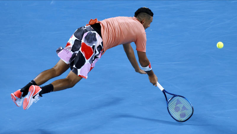 Australia's Nick Kyrgios is airborne as he attempts to return a shot to Spain's Rafael Nadal during their fourth round singles match at the Australian Open tennis championship in Melbourne, Australia, Monday, Jan. 27, 2020. (AP Photo/Andy Wong)