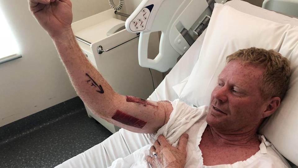 Paul Kenny escaped serious injury after punching a shark that attacked him north of Newcastle