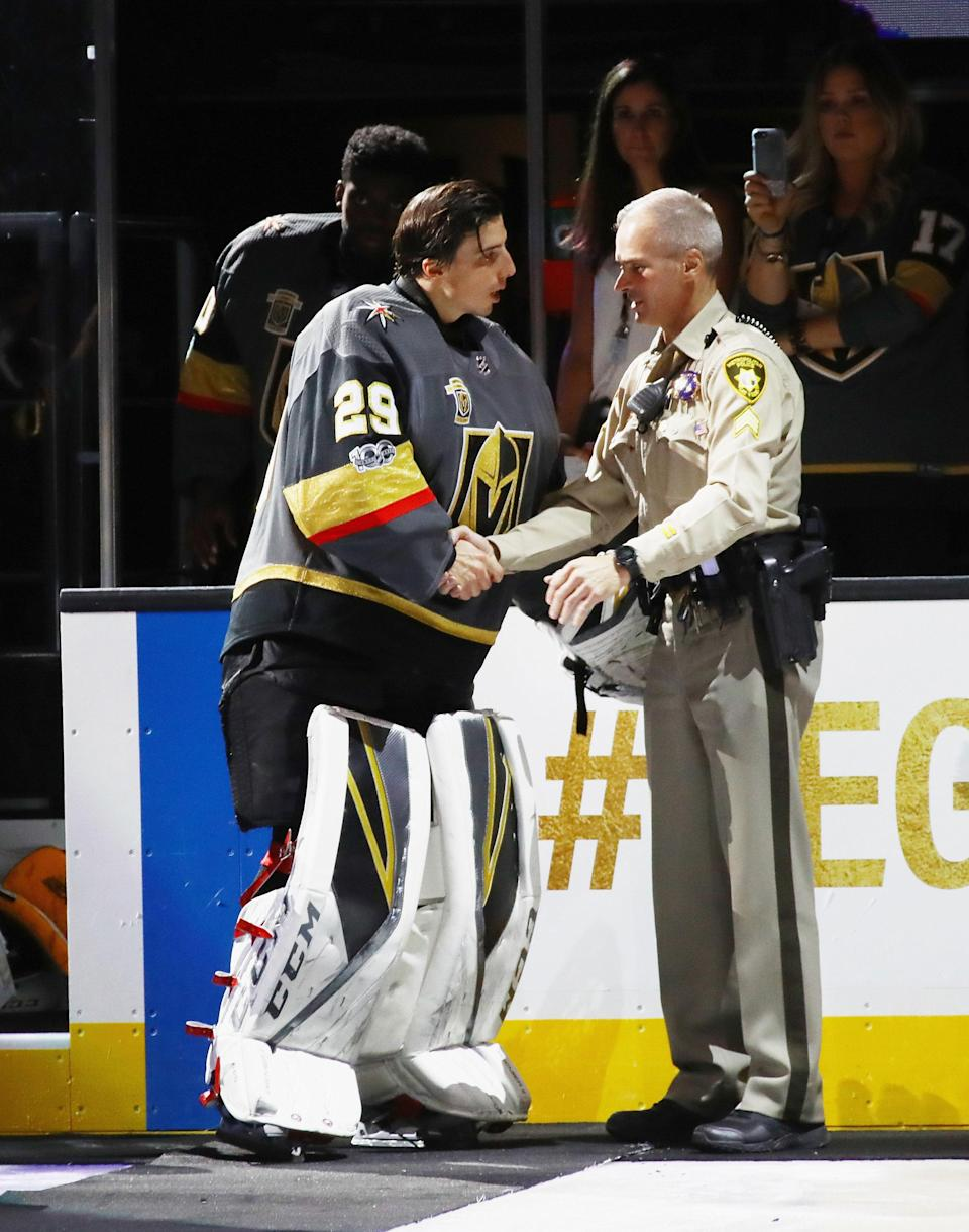 <p>Golden Knights goaltender Marc-Andre Fleury shares a moment with a first responder before puck drop. (Bruce Bennett/Getty Images) </p>