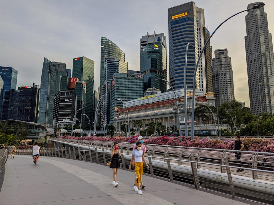 May 2020. Singapore. Scene of everyday Singapore during the world pandemic of 2020 Coronavirus / COVID - 19 people walking with masks one and exercising while a architectural marvel stands in the background (The Esplanade Theater) aka the Durian. A woman puts on a red facemask while walking with her friends.