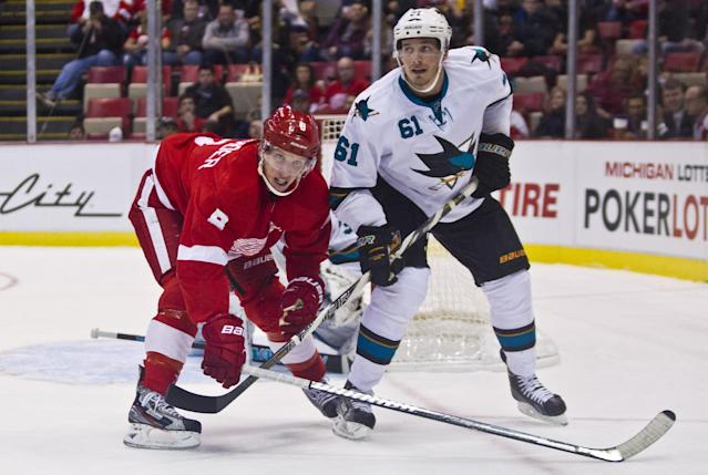 Detroit Red Wings forward Justin Abdelkader (8) and San Jose Sharks forward Tyler Kennedy (81) lock sticks as they follow the puck, during the first period of an NHL hockey game in Detroit, Mich., Monday, Oct. 21, 2013. (AP Photo/Tony Ding)