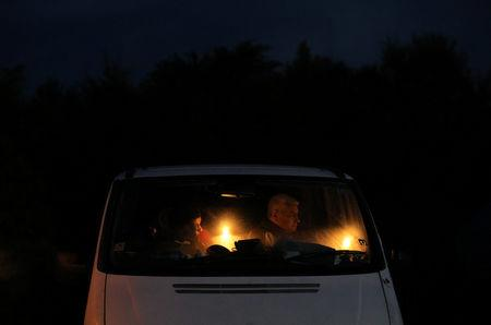 Orthodox Christian pilgrims hold candles inside a minibus on the eve of the Elevation of the Cross holiday at Krustova Gora (Holly Cross Forest), Bulgaria, September 13, 2018. REUTERS/Stoyan Nenov