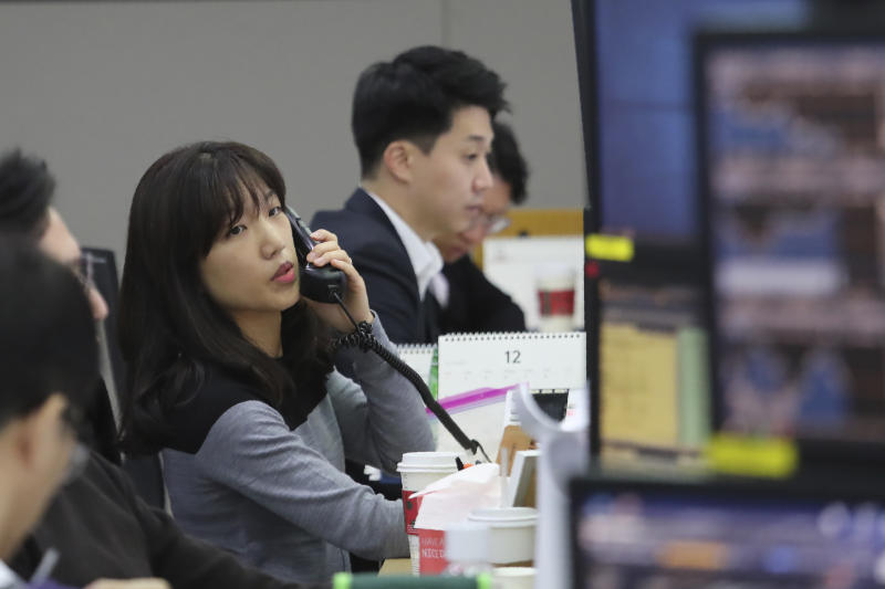 A currency trader talks on the phone at the foreign exchange dealing room of the KEB Hana Bank headquarters in Seoul, South Korea, Monday, Dec. 9, 2019. Asian shares were mostly higher Monday cheered by a buying mood on Wall Street that came at the end of last week. (AP Photo/Ahn Young-joon)