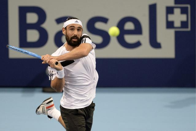 Cyprus' Marcos Baghdatis returns a ball to Argentina's Juan Martin Del Potro during their second round match at the Swiss Indoors tennis tournament at the St. Jakobshalle in Basel, Switzerland, on Thursday, Oct. 24, 2013. (AP Photo/Keystone,Georgios Kefalas)