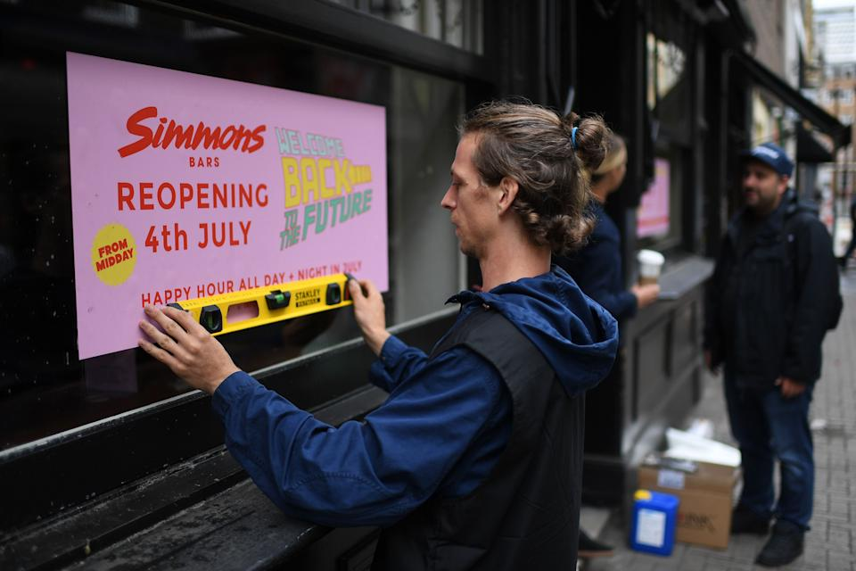 A man works to affix a sign advertising the planned July 4 re-opening of a bar in Soho in London on June 30, 2020, as coronavirus lockdown measures continue to be eased. - Pubs and restaurants will on July 4 be allowed to reopen, as will hotels, bed and breakfasts, self-catering accommodation and campsites, alongside cinemas, museums and galleries. (Photo by DANIEL LEAL-OLIVAS / AFP) (Photo by DANIEL LEAL-OLIVAS/AFP via Getty Images)
