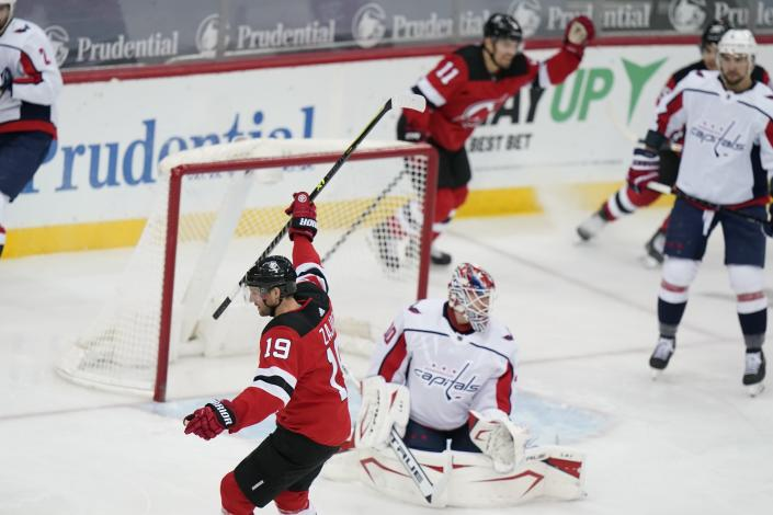 New Jersey Devils' Travis Zajac (19) celebrates as he skates past Washington Capitals goaltender Ilya Samsonov (30) after scoring a goal during the first period of an NHL hockey game Sunday, April 4, 2021, in Newark, N.J. (AP Photo/Frank Franklin II)