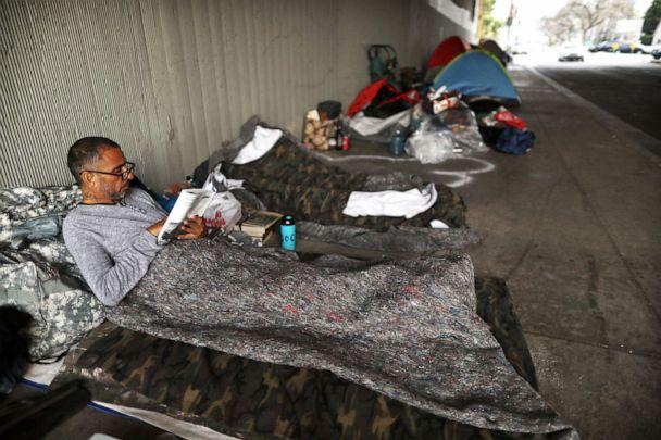 PHOTO: Travis Stanley, who said he has been homeless for three months and is a U.S. Navy veteran, reads on donated bedding where he normally sleeps beneath an overpass on June 5, 2019, in Los Angeles. (Mario Tama/Getty Images, FILE)