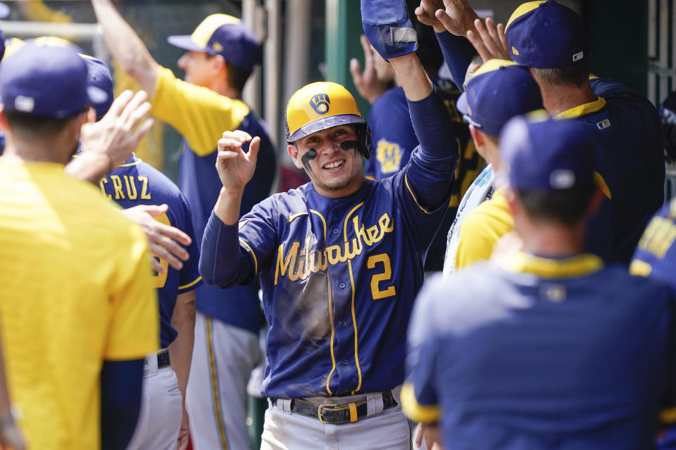Milwaukee Brewers' Luis Urias (2) celebrates with teammates after scoring a run during the fifth inning of a baseball game against the Cincinnati Reds in Cincinnati, Sunday, July 18, 2021. (AP Photo/Bryan Woolston)