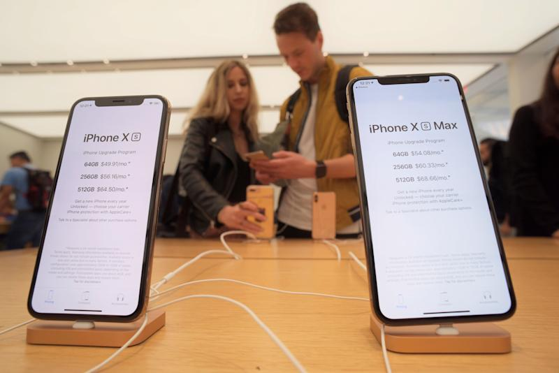 Customers look at new Apple iPhones including the iPhone XS, left, iPhone XS Max on display at an Apple store in New York on Friday, Sept. 21, 2018. (AP Photo/Patrick Sison)