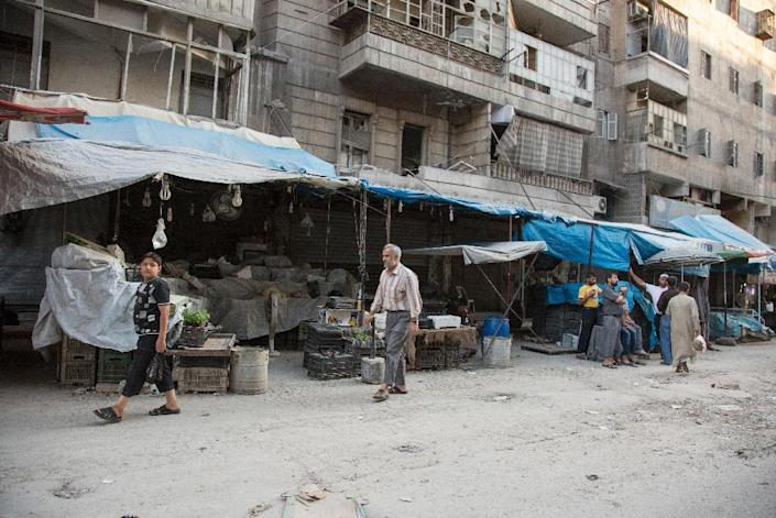 Syrians walk past an empty vegetable market in the rebel-held area of the northern Syrian city of Aleppo on July 10, 2016 after the regime closed the Castello Road severing the supply route to the opposition-held eastern half of the city (AFP Photo/Karam Al-Masri)