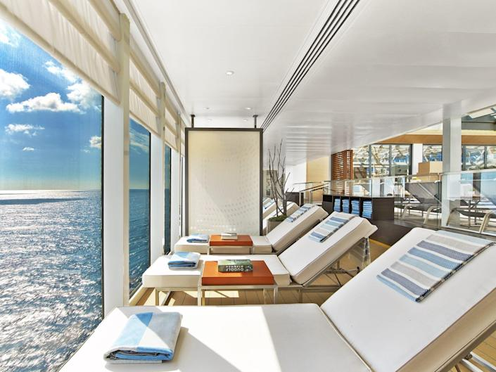 lounge chairs facing a glass wall with a view of the ocean