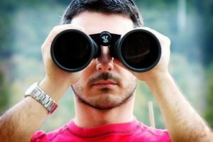 Guy looking through binoculars
