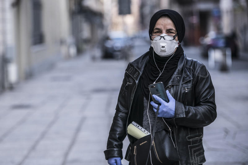TURIN, ITALY - MARCH 18: Woman with mask and gloves walks while using a smartphone as Italy continues it nationwide lockdown to control coronavirus pandemic on March 18, 2020 in Turin, Italy. The Italian government continues to enforce the nationwide lockdown measures to control the spread of COVID-19. (Photo by Stefano Guidi/Getty Images)