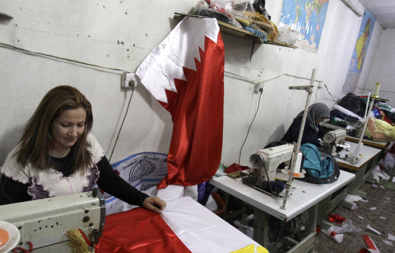 In this photo dated March 25, 2011, women work in a basement workshop in central Baghdad, Iraq, making Bahrain national flags.  The sewing machines have been working hard to produce the red and white Bahraini flags which are proving to be very popular for Iraqi protesters to wave at demonstrations, unfurl from buildings and fly from car antennas. The fervor for the Bahrain national symbol is testimony to the solidarity which Iraqi Shiites feel with their religious brethren in Bahrain battling for more rights.(AP Photo/Khalid Mohammed)