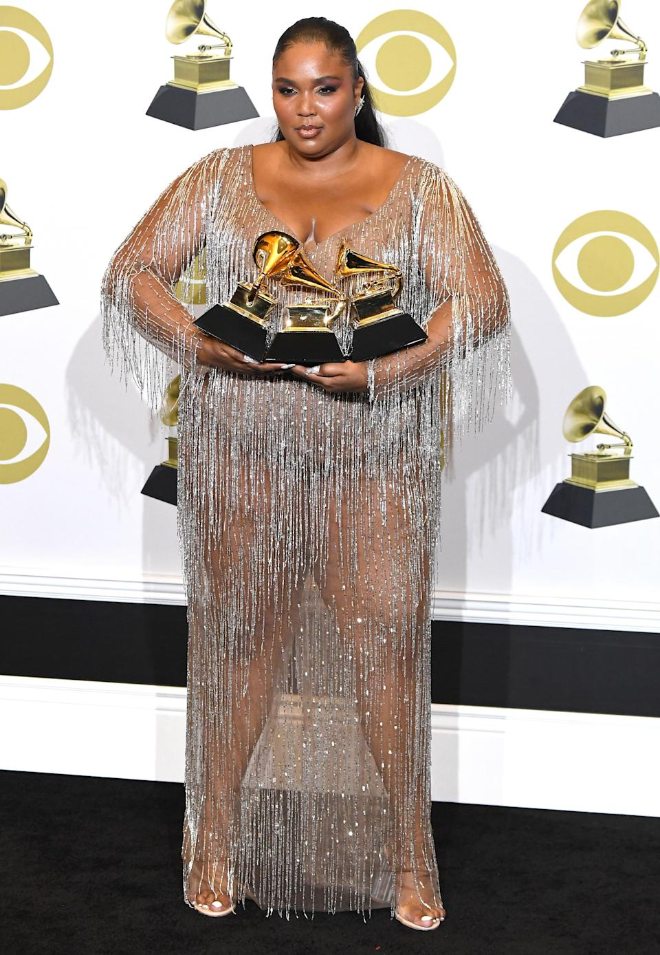 The last outfit change of the night was a custom Atelier Versace sheer dress. Her standout accessories just so happened to be three Grammys.