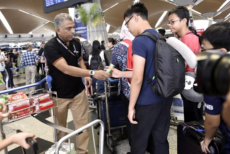 Malaysian Airport personnel distribute refreshments to passengers at the Kuala Lumpur International Airport August 24,2019.
