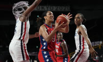United States' A'Ja Wilson (9), center, drives past France's Endene Miyem (5), left, during women's basketball preliminary round game at the 2020 Summer Olympics, Monday, Aug. 2, 2021, in Saitama, Japan. (AP Photo/Eric Gay)