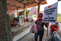 Man donning superhero costume brings cheer to children confined to their homes by COVID-19 restrictions in Sukoharjo