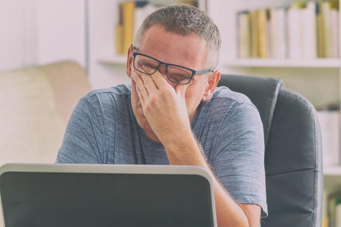 Man sitting at laptop, rubbing his eyes under his glasses.