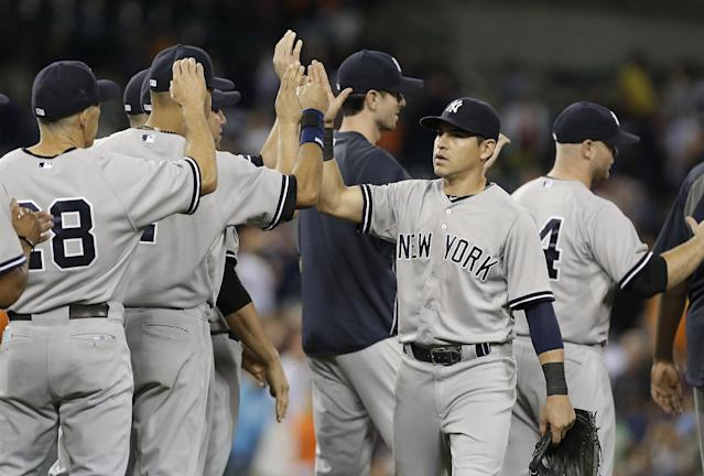 New York Yankees' Jacoby Ellsbury congratulates teammates after they defeated the Detroit Tigers 8-4 in a baseball game in Detroit, Wednesday, Aug. 27, 2014. (AP Photo/Paul Sancya)