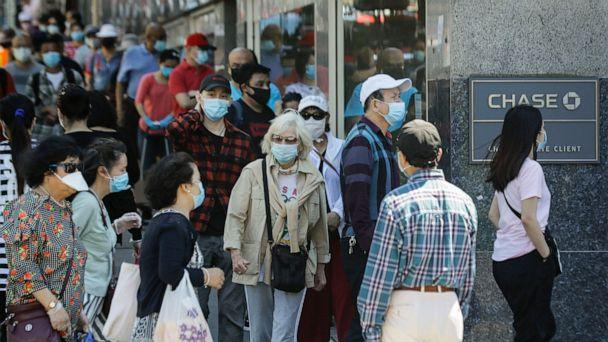 PHOTO: Patrons wearing protective masks wait to enter a Chase bank location, June 8, 2020, in the Queens borough of New York. After three bleak months, New York City will try to turn a page and begin reopening Monday after getting hit by the coronavirus. (Frank Franklin II/AP)