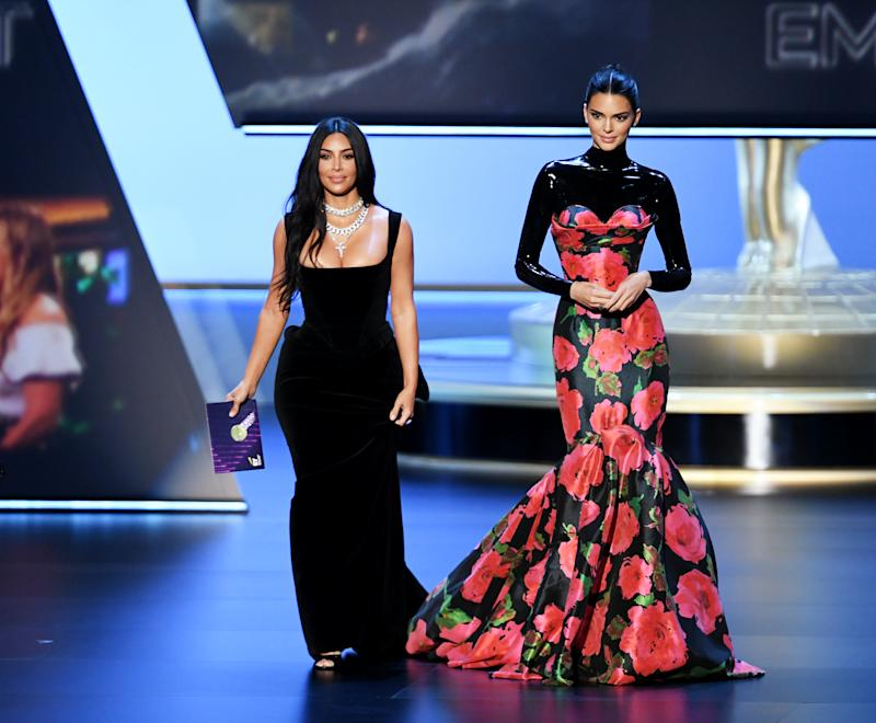 Kim Kardashian and Kendall Jenner walk on stage at the 2019 Emmy Awards