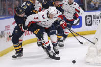 Buffalo Sabres forward Curtis Lazar (27) and Washington Capitals defenseman Nick Jensen (3) battle for the puck during the first period of an NHL hockey game Monday, March 9, 2020, in Buffalo, N.Y. (AP Photo/Jeffrey T. Barnes)