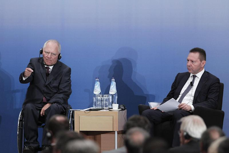 German Finance Minister Wolfgang Schaeuble, left, speaks next to Greek Finance minister Yannis Stournaras during a German-Greek chamber of industry and trade event, in Athens, Thursday, July 18, 2013. More than 4,000 police officers were on duty Thursday for a visit to Athens by Schaeuble, as the government banned demonstrations across the city after Parliament agreed overnight to more austerity measures. (AP Photo/Petros Giannakouris)