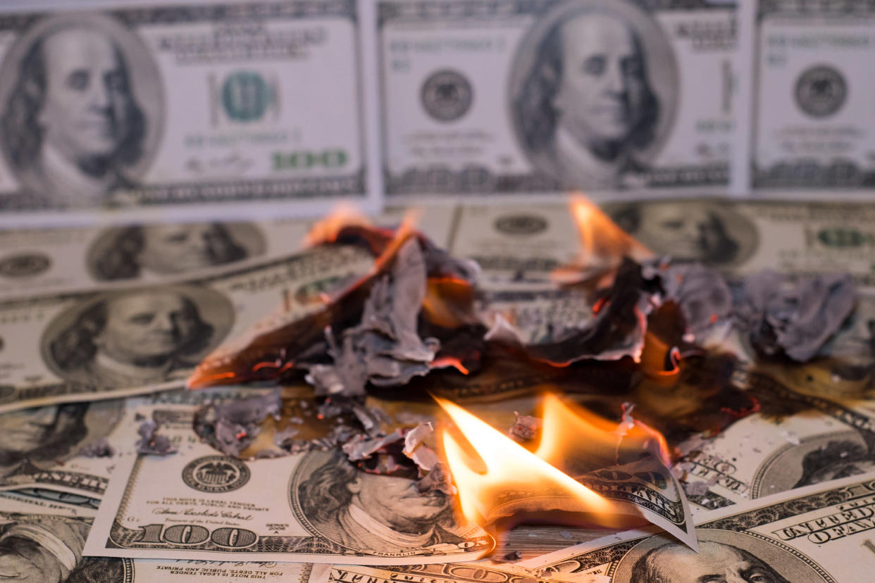 A small pile of hundred dollar bills on fire, with a wallpaper of hundred dollar bills in the background.