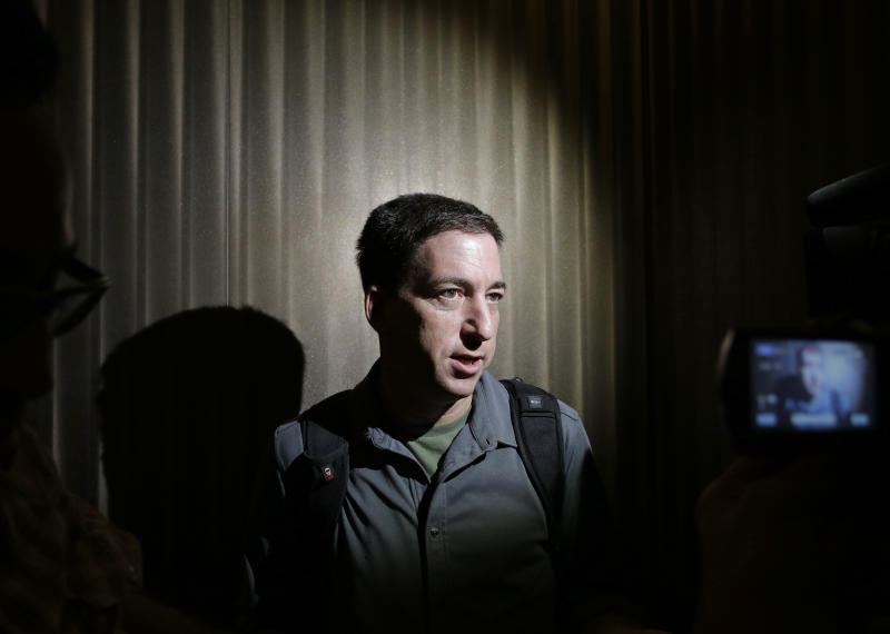 Glenn Greenwald, right, a reporter for The Guardian newspaper, speaks to media at a hotel in Hong Kong Monday, June 10, 2013. Greenwald spoke about his interview with Edward Snowden, the 29-year-old contractor who allowed himself to be revealed as the source of disclosures about the U.S. government's secret surveillance programs. (AP Photo/Vincent Yu)