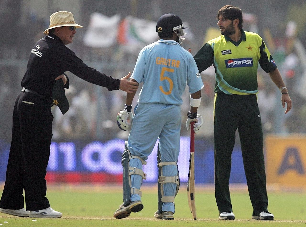 Indian cricketer Gautam Gambhir (C) and Pakistan's Shahid Afridi (R) exchange words during their third One-day International (ODI) match at the Green Park Stadium in Kanpur, 11 November 2007.  Pakistan captain Shoaib Malik won the toss and sent India in to bat in the third one-day international at the Green Park as the five-match series is tied at 1-1.       AFP PHOTO/ MANAN VATSYAYANA