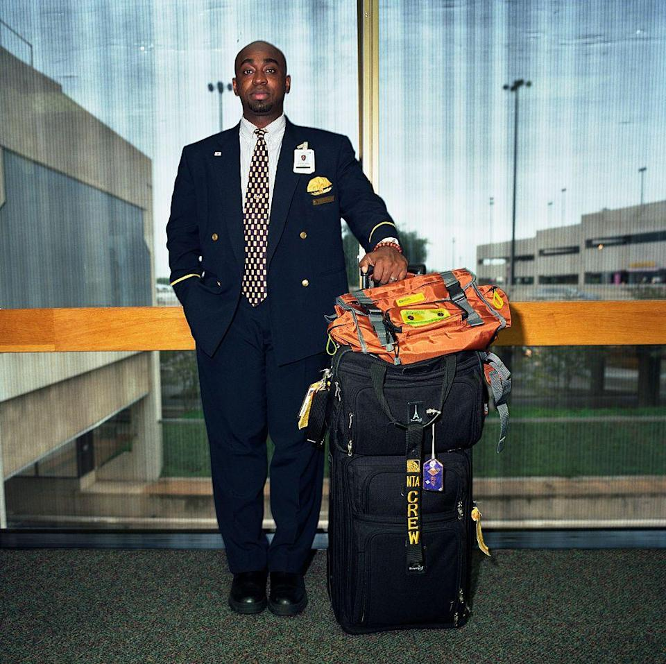 <p>An American Airlines flight attendant with his crew baggage during a layover at Dallas Fort Worth airport.</p>
