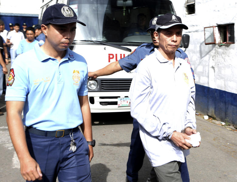 In this photo released by the Philippine National Police Public Information Office, suspected communist leader, Benito Tiamzon, right, is escorted as he arrives at Camp Crame police headquarters in suburban Quezon city, north of Manila, Philippines on Sunday March 23, 2014. Philippine officials said Sunday that they would not release two leaders of a violent rebel group fighting to overthrow the government, whose arrests were a serious blow to one of Asia's longest-running communist insurgencies. (AP Photo/Philippine National Police, Public Information Office)
