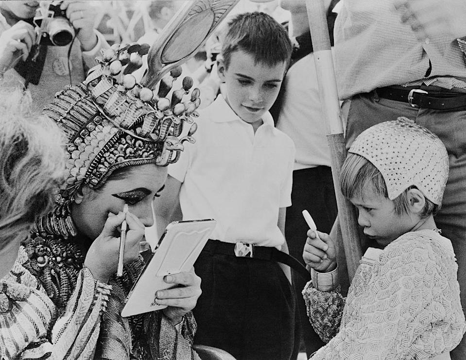 <p>Elizabeth frequently brought her children to the set of her films. Here, she applies makeup for a scene in <em>Cleopatra</em> in 1962 as her son, Christopher Wilding, looks on.</p>