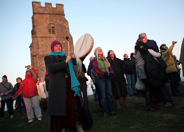 GLASTONBURY, ENGLAND - MAY 01: People watch the sun rise as they join in a Beltane dawn celebration service in front of St. Michael's Tower on Glastonbury Tor on May 1, 2013 in Glastonbury, England. Although more synonymous with International Workers' Day, or Labour Day, May Day or Beltane is celebrated by druids and pagans as the beginning of summer and the chance to celebrate the coming of the season of warmth and light. Other traditional English May Day rites and celebrations include Morris dancing and the crowning of a May Queen with celebrations involving a Maypole. (Photo by Matt Cardy/Getty Images)