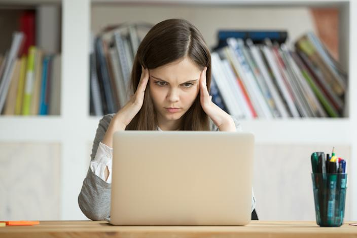 Focused concerned student learning difficult homework assignment with laptop online, concentrated girl preparing for digital exam on pc, serious young woman thinking hard on task with computer