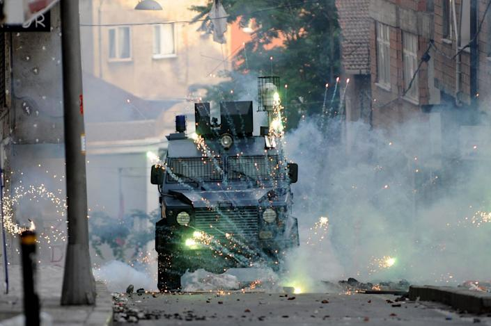 Fireworks thrown by Kurdish protestors burst in front of a riot police vehicle during a clashes with riot police on June 8, 2014 at Okmeydani district in Istanbul (AFP Photo/Ozan Kose )
