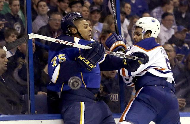 St. Louis Blues' Ryan Reaves, left, is checked into the boards by Edmonton Oilers' Mark Fraser during the second period of an NHL hockey game Thursday, March 13, 2014, in St. Louis. (AP Photo/Jeff Roberson)